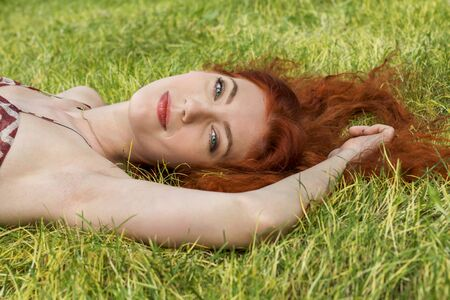 high spirited: Close up Very Happy Young Woman Lying on Grassy Ground Stock Photo