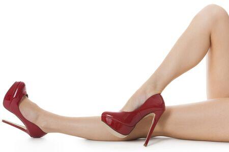 piernas sexys: Flawless mujer en las piernas elegantes zapatos rojos del alto tal�n, aislado sobre fondo blanco.