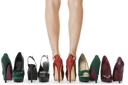 bare women: Close up Flawless Woman Legs in Glossy Red High Heel Shoes Standing Between Other Elegant High Heels. Isolated on White Background.