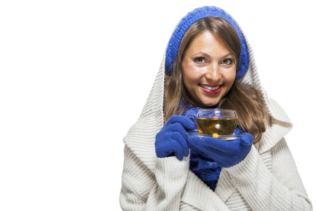 cowl: Fashionable young woman in a blue knitted cowl neck jersey winter ensemble and sipping a cup of hot tea with a smile in a effort to keep warm, isolated on white
