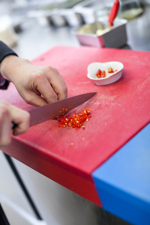 caterers: Chef dicing red hot chili peppers on a chopping board in a commercial kitchen for use as a spicy flavoring in his recipes as he cooks the evening meal