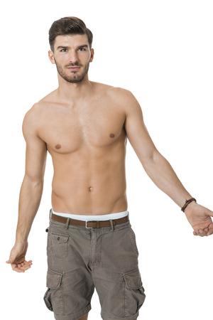 uomo nudo: Bello senza camicia nuda barbuto giovane uomo in piedi guardando intensamente la fotocamera con la mano al mento in una posa sexy sensuale, isolato su bianco
