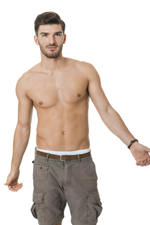 naked man: Handsome shirtless naked bearded young man standing looking intently at the camera with his hand to his chin in a sensual sexy pose, isolated on white Stock Photo