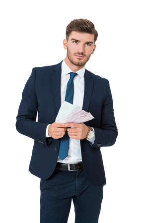 affluence: Wealthy stylish successful young businessman burning money from a handful of euro banknotes with a happy smile showing off his affluence, isolated on white Stock Photo