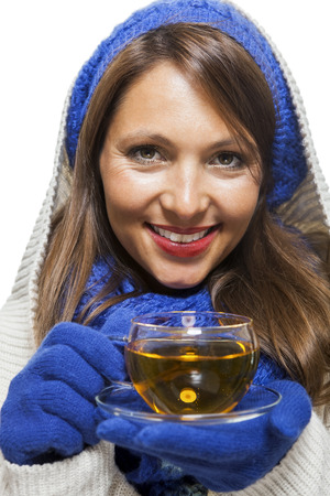 Fashionable young woman in a blue knitted cowl neck jersey winter ensemble and sipping a cup of hot tea with a smile in a effort to keep warm, isolated on white photo