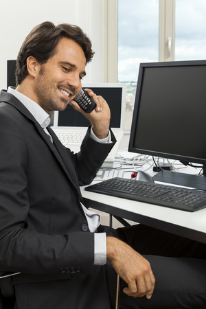 businessman working at his computer: Successful businessman working in his office sitting in a chair at his desk and desktop computer listening to a call on his mobile phone, high angle side view