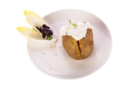endivia: Vista de arriba de un horno de patatas al horno chaqueta saludable con salsa de crema agria adornado con hojas de escarola y hierbas frescas