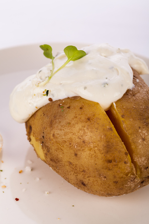 jacket potato: Overhead view of a healthy oven baked jacket potato with sour cream sauce garnished with endive leaves and fresh herbs Stock Photo