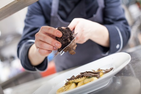 Chef grating truffle mushroom shavings onto homemade ravioli in a restaurant kitchen while preparing a dinner, close up view of the counter, plate and hands