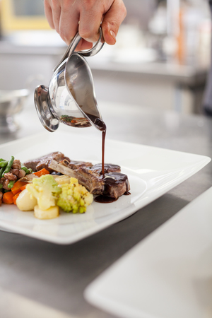 Chef plating up food in a restaurant pouring a gravy or sauce over the meat before serving it to the customer, close up view of his hand and the gravy boat photo