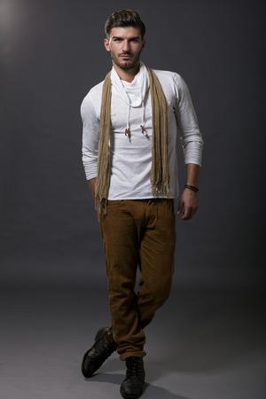 bel homme: Suave sexy beau �l�gant jeune homme en v�tements casual chic avec une �charpe prenant une pose nonchalante macho comme il donne la sulfureuse de la cam�ra regarde Banque d'images
