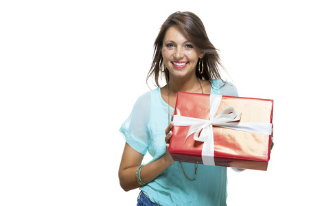 giftwrapped: Close up portrait of happy young woman in casual clothing holding a red big gift box with white ribbon while looking at the Camera.