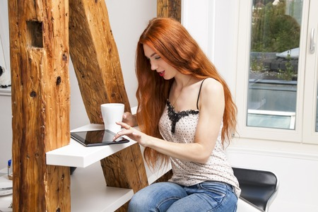 e pretty: Pretty young blond woman sitting near the window with a glass of drink and a tablet computer.