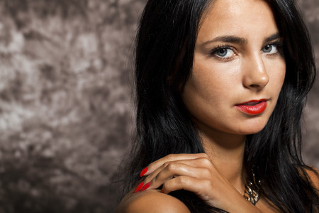 attractive charismatic: Close up Pretty Young Woman with long Black Hair, Wearing Red. Looking at Right Frame. Captured with Abstract Brown Background.