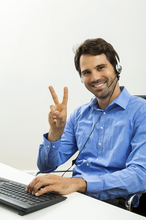 young unshaven: Attractive unshaven young man wearing a headset offering online chat and support on a client services of help desk as he types in information on his computer