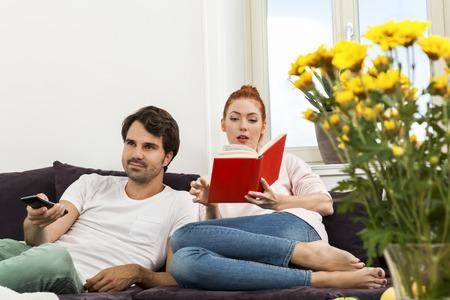 mujer viendo tv: Pareja joven descansando en el sofá en la sala de estar mientras que el hombre está mirando la televisión y la mujer está leyendo un libro. Foto de archivo