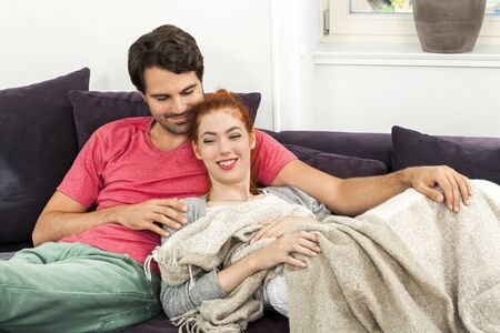 Young Couple Resting on the Sofa at the Living Room While the Man is Watching TV and Woman is Reading a Book. photo