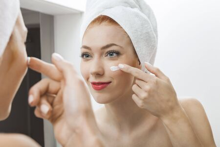 routine: Close up Fresh Woman After Shower Applying White Cream on her Face in Front a Mirror With Towel on her Head.