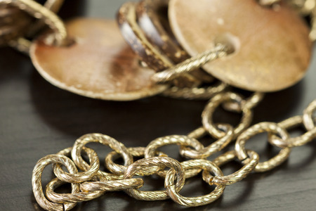 interlinked: Scratched and tarnished old silver jewellery with two flat discs flanking a ring suspended on an oval link chain, close up view on a grey