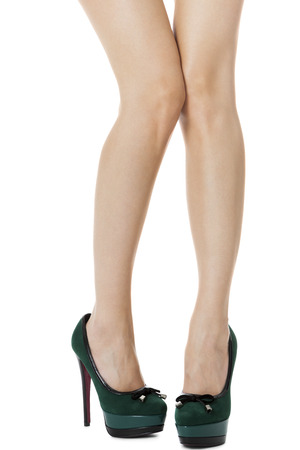 flawless: Close up Sexy Flawless Woman Legs in Green High Heel Shoes with One Leg Lifted and Crossing the Other Leg. Isolated on White Background. Stock Photo