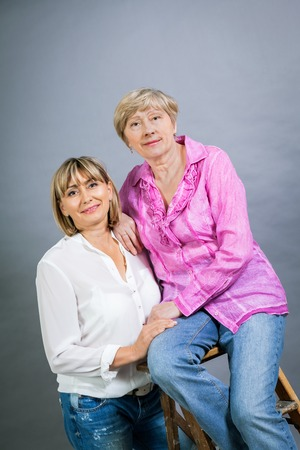 resemblance: Attractive stylish blond senior lady with her beautiful middle-aged daughter posing together with her hands on her shoulders smiling at the camera on a grey studio  Stock Photo
