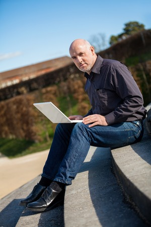 balding: High angle profile view of a balding middle-aged man sitting on a wooden bench using a laptop computer Stock Photo