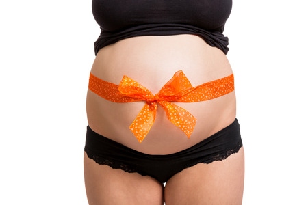 bow belly: Pregnant woman wearing a colorful orange ribbon and bow wrapped around her belly conceptual of the gift of childbirth and the unborn baby, close up of her swollen tummy isolated on white