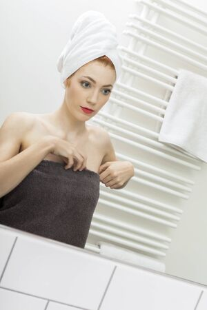 unblemished: Close up Fresh Young Woman From Shower Looking her Face While Touching it In Front the Mirror