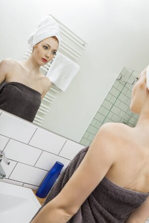 Close up Fresh Young Woman From Shower Looking her Face While Touching it In Front the Mirror photo