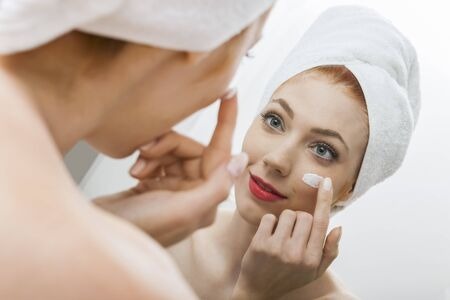 unblemished: Close up Fresh Woman After Shower Applying White Cream on her Face in Front a Mirror With Towel on her Head.