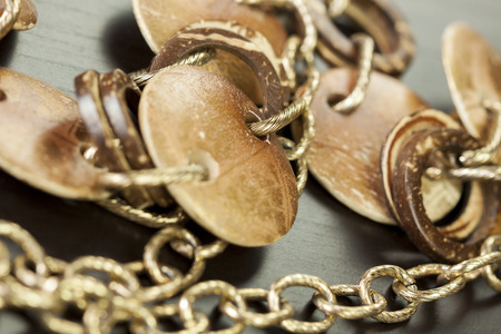costume jewellery: Scratched and tarnished old silver jewellery with two flat discs flanking a ring suspended on an oval link chain, close up view on a grey