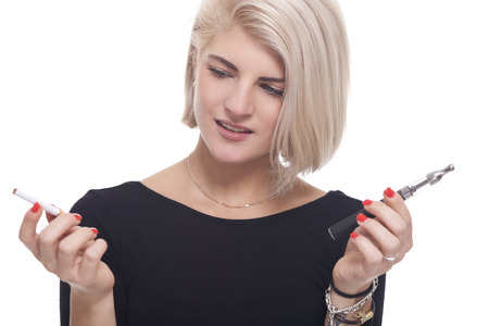 atomiser: Close up Young Blond Woman in Black Clothing Holding a Tobacco and E-Cigarette on a White .