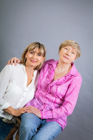 resemblance: Attractive stylish blond senior lady with her beautiful middle-aged daughter posing together with her hands on her shoulders smiling at the camera on a gray studio