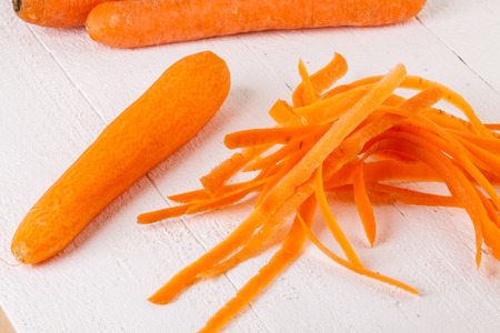 cooking implement: Fresh peeled carrots sliced into thin batons for carrot julienne with a metal kitchen cutter on a white