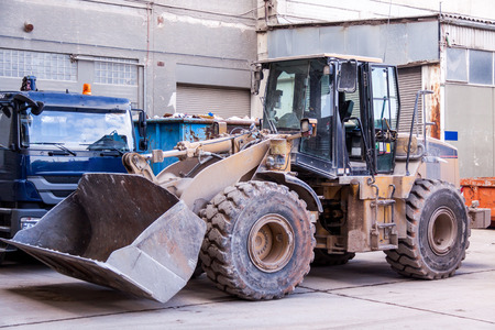 earth moving equipment: Front end loader with its bucket or scoop down parked in front of a warehouse on paving