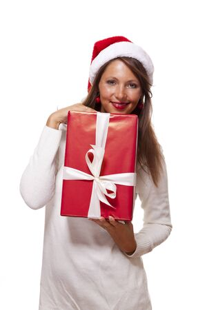 Pretty woman in a festive red Santa hat with a large matching red Christmas gift tied with a ribbon and bow holding it in front of her with a happy smile showing it to the camera, on white Reklamní fotografie