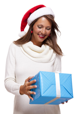 giftwrapped: Beautiful vivacious woman wearing a red Santa hat laughing and holding up a gift-wrapped blue Christmas gift as she celebrates the festive season, on white