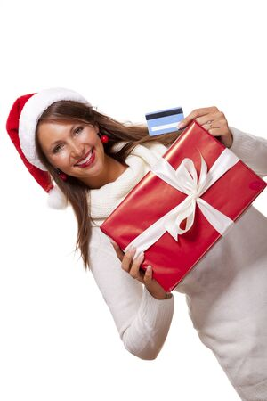 giftwrapped: Attractive woman with a lovely smile wearing a red Santa hat holding a big red Christmas gift box and bank card as she celebrates her successful shopping spree Stock Photo