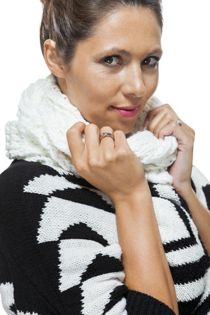 snuggling: Attractive elegant woman in winter fashion snuggling down into her white scarf and black and white jumper to ward off the cold winter weather, on white Stock Photo