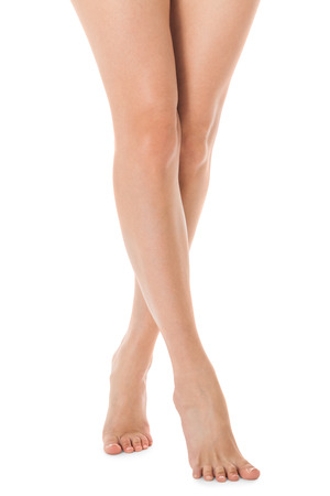 young feet: Elegant crossed long bare shapely female legs with bare feet viewed from above isolated on white with copyspace