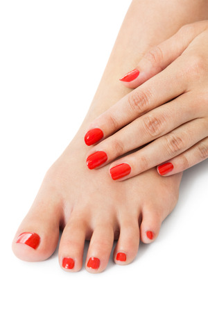 cosmetic lacquer: Woman with beautiful neatly manicured red finger and toenails sitting with bare feet clasping her ankles to display her nails, closeup on white in a fashion and beauty concept