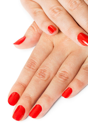 gracefully: Woman with beautiful manicured red fingernails gracefully crossing her hands to display them to the viewer on a white background in a fashion, glamour and beauty concept