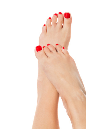 pedicure: Sexy slender female feet with carefully pedicured fashionable red nails displayed in the crossed position on white with copyspace Stock Photo