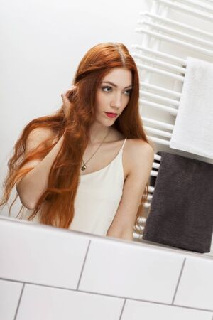 musing: Close up Mirror Reflection of a Gorgeous Young Woman While Touching her Long Blond Hair