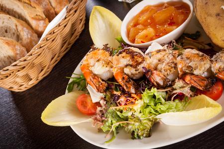 escarola: Gambas a la plancha con una lechuga de hoja verde y ensalada de escarola y una chaqueta patatas coronado con crema agria servido en un plato blanco, opini�n de alto �ngulo en blanco