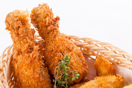 Crisp crunchy golden chicken legs and wings deep fried in bread crumbs and served with a bowl of dip in a wicker basket for a delicious appetizer