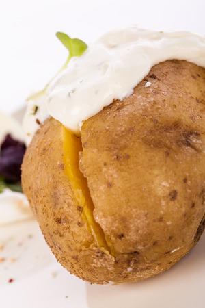 escarola: Vista de arriba de un horno de patatas al horno chaqueta saludable con salsa de crema agria adornado con hojas de escarola y hierbas frescas