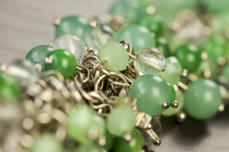 silver jewellery: Close up view of pretty translucent green beads on an item of silver jewellery attached in a bunch to a ring by short chains with shallow dof in a fashion concept