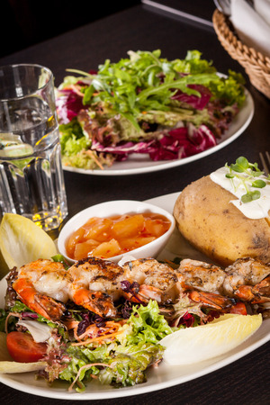jacket potato: Grilled prawns with a green leafy lettuce and endive salad and a jacket potato topped with sour cream served on a white plate, close up high angle view on white Stock Photo