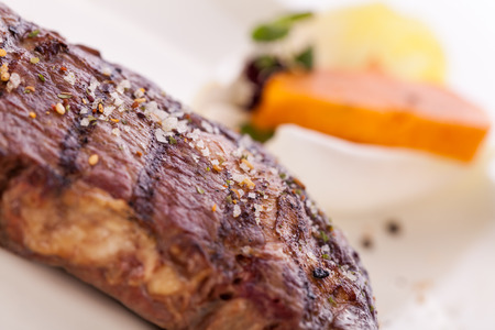 trimmed: Delicious trimmed lean portion of thick grilled beef steak with seasoning served on a white plate, close up with shallow dof